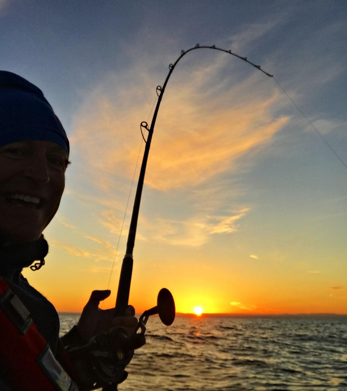 Herlig solnedgang med fisk i enden av stangen